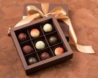 在工艺箱子的美好的巧克力有在黑暗的背景的缎带的 平的布局 欢乐概念 复制空间 免版税库存照片