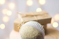在工艺纸包裹的圣诞礼物箱子栓与麻线亚麻布织品在木椅子的装饰品球 金黄诗歌选bokeh光 免版税库存照片