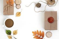 在工艺纸包裹的手工制造礼物和烘干在白色背景的叶子 免版税库存图片