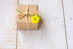 在工艺纸包裹的礼物盒栓与麻线,反弹黄色花,顶视图 免版税库存照片
