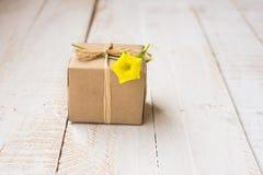 在工艺纸包裹的礼物盒栓与麻线,反弹黄色花 库存图片