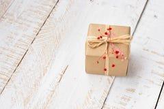在工艺纸包裹的礼物盒栓与麻线,嫩小红色花,顶视图 库存照片