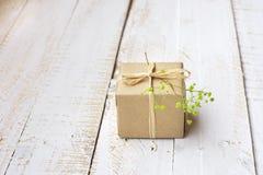 在工艺纸包裹的礼物盒栓与麻线,嫩小绿色花,顶视图 库存照片