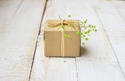 在工艺纸包裹的礼物盒栓与麻线,嫩小绿色花 图库摄影