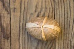 在工艺纸包裹的被手工造的装饰复活节彩蛋栓与在板条木头背景的麻线 免版税库存照片