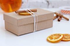 在工艺纸和干桔子包裹的手工制造礼物在白色背景 免版税图库摄影