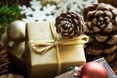 在工艺纸圣诞节和新年包裹的礼物盒,杉木锥体,五颜六色的球,木装饰品雪剥落,土气样式 免版税库存照片