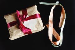 在工艺纸的美好的简单的礼物与各种各样的丝带和 库存照片