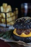 在工艺纸的黑汉堡 免版税库存图片