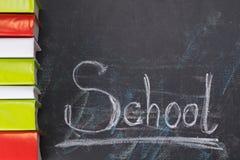 在左边谎言垂直写的词学校和黑板上连续书 免版税库存照片