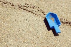 在左铁锹玩具之后的海滩 库存图片