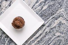 在巧克力杯子蛋糕上的平的位置在灰色花岗岩背景上的白方块板材 免版税库存图片