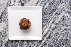 在巧克力杯子蛋糕上的平的位置在灰色花岗岩背景上的白方块板材 库存照片