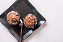 在巧克力杯子蛋糕松饼上的平的位置在黑角规板材 免版税库存照片
