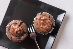 在巧克力杯子蛋糕松饼上的平的位置在黑角规板材 免版税库存图片
