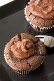 在巧克力杯子蛋糕松饼上的平的位置在黑角规板材 库存图片