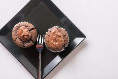 在巧克力杯子蛋糕松饼上的平的位置在黑角规板材 库存照片