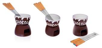 在巧克力涮制菜肴的盘与蘸在巧克力的果子的叉子 免版税库存图片