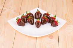 在巧克力的草莓在白色板材 免版税库存照片