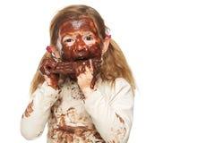 在巧克力盖的一个小女孩吃巧克力块的和面孔的画象 免版税库存照片