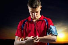 在巧妙的手表的青少年的男孩reviewong体育活动 库存照片