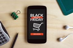 在巧妙的电话屏幕上的黑星期五概念在木书桌上 免版税库存照片