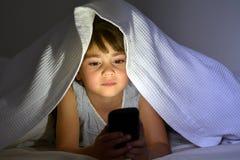 在巧妙的电话的小孩戏剧在盖子下的床上在附近 免版税库存照片