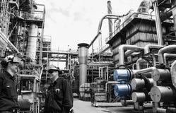 在巨人里面的精炼厂工作者用管道运输建筑 免版税图库摄影