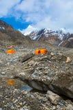 在巨型冰川垂直的橙色山帐篷 库存图片