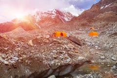 在巨型冰川的橙色山帐篷 免版税库存照片