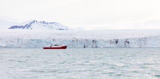 在巨型的冰川前面的远征小船 免版税库存图片