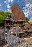 在巨大的岩石附近的泰国小屋 免版税图库摄影