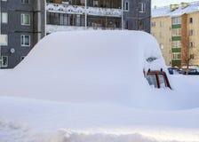 在巨大的随风飘飞的雪下的汽车 库存照片