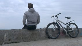 在巨大的风暴期间,有自行车的一个孤立人坐老高具体码头 股票视频