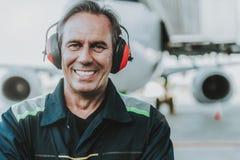 在巨大的飞机前面的微笑的英俊的技工身分 图库摄影