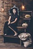 在巫婆服装的女孩childl用南瓜和糖果在霍尔 免版税库存图片