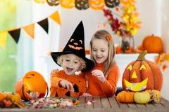 在巫婆服装的孩子在万圣夜把戏或款待 免版税图库摄影