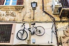 在巴勒莫,西西里岛,意大利骑自行车垂悬在老墙壁上 库存照片