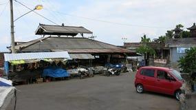 在巴厘岛的传统市场大厦在印度尼西亚 与销售物品的摊位 摩托车、滑行车和汽车的停车处 ?? 库存图片