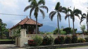 在巴厘岛的传统建筑学在印度尼西亚 一个房子的看法有一个庭院的有热带植被和棕榈树的 免版税库存照片