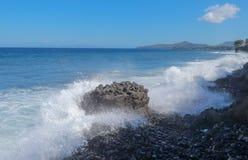 在巴厘岛附近的印度洋海岸线 击中石海滩和攻击岩石海岸喷水的大波浪 免版税库存照片