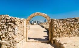 在巴林堡垒的古老曲拱与麦纳麦地平线  科教文组织世界遗产 库存照片