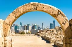 在巴林堡垒的古老曲拱与麦纳麦地平线  科教文组织世界遗产 图库摄影