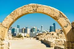 在巴林堡垒的古老曲拱与麦纳麦地平线  科教文组织世界遗产 免版税库存照片