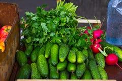 在市场上的柜台用黄瓜和绿色 库存照片