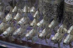 在市场上的金属鱼站立,柬埔寨的传统工艺 游人Koi鲤鱼金属小雕象的纪念品店 图库摄影