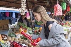 在市场上的长的头发女孩与菜 免版税图库摄影