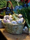 在市场立场的新鲜的大蒜用春天葱 免版税库存照片