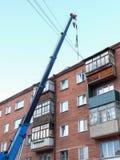 在市鄂木斯克顶房顶修理一栋五层砖瓦房 免版税库存照片