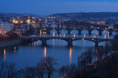 在布拉格桥梁的晚上在伏尔塔瓦河河的图片和河岸有包括的查尔斯桥梁的 免版税库存照片